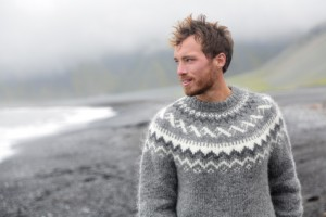 Handsome man walking black sand beach on Iceland wearing Icelandic sweater. Good looking male model looking pensive at ocean sea.