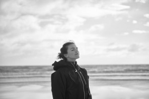 Young woman standing with her eyes closed on a cold winter day on the beach breathing in the fresh air