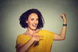 Closeup portrait fit middle aged healthy model woman flexing muscles confident showing her strength isolated on gray background. Positive emotion facial expression feeling attitude perception