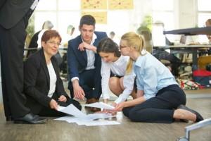 Business Team sortiert Dokumente auf dem Boden im Büro